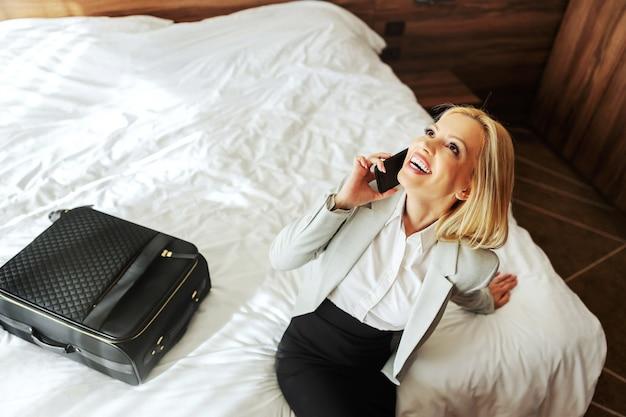 Vista superior de la sonriente mujer de mediana edad sentada en la cama en una habitación de hotel y tener una conversación telefónica con alguien.