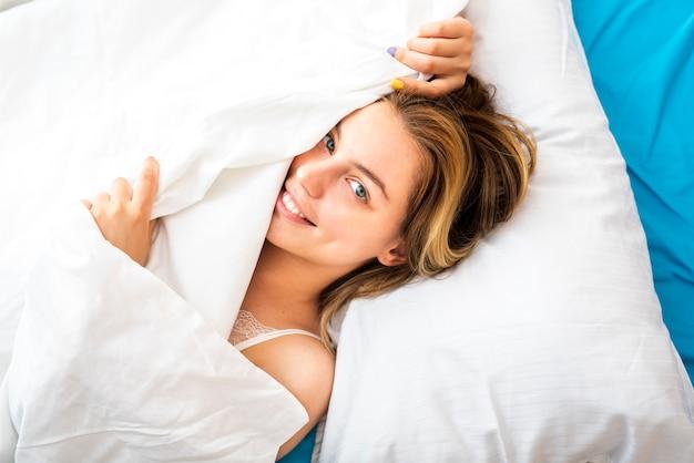 Vista superior sonriente mujer tirando la sábana sobre la cara