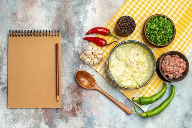 Vista superior de sopa de albóndigas de dushbara en un tazón de fuente de ajo pimientos picantes cuencos de cuchara de madera con carne pimienta y verduras un cuaderno en la mesa desnuda