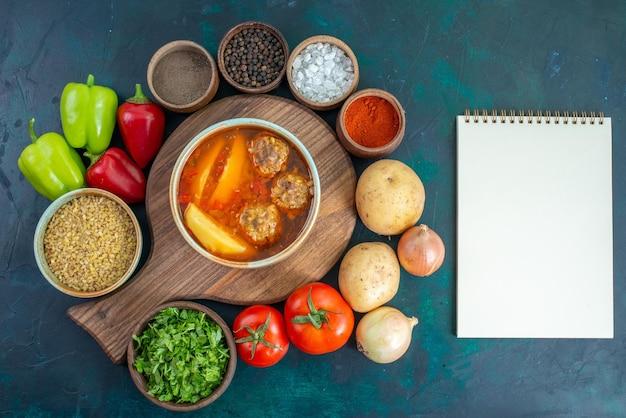 Vista superior de sopa de albóndigas con patatas en rodajas dentro y con verduras frescas en el escritorio azul oscuro