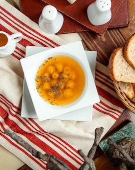 Vista superior de la sopa de bola de masa de dushbara adornada con menta seca