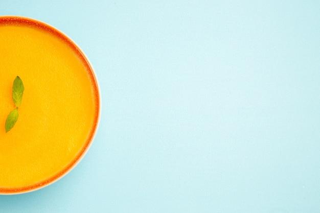 Vista superior de la sopa de calabaza dentro de la placa sobre el fondo azul.