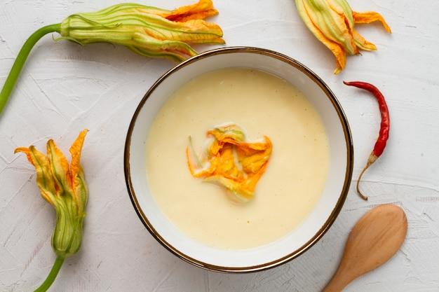 Vista superior sopa de calabaza con flores secas