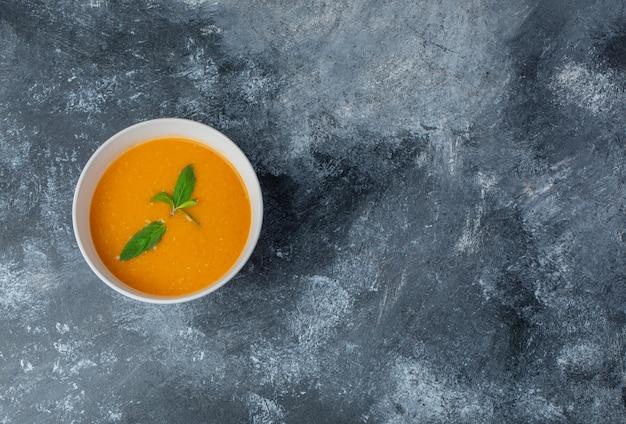 Vista superior de sopa casera fresca en un tazón blanco sobre mesa gris