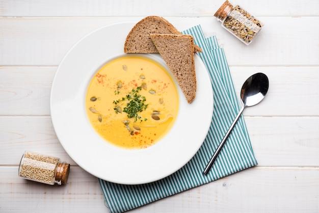 Vista superior de sopa de crema con rebanadas de pan y semillas