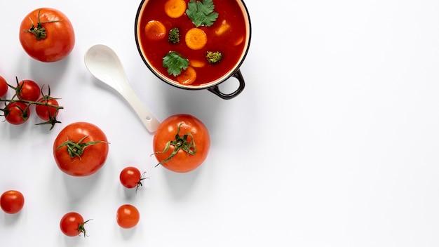 Vista superior de sopa y cuchara de tomate