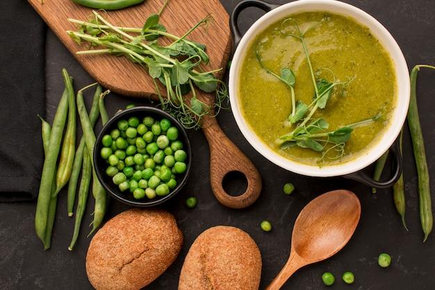 Vista superior de la sopa de guisantes de invierno con pan y cuchara