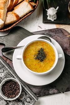 Vista superior de sopa de guisantes y lentejas con azafrán y hierbas en un tazón blanco