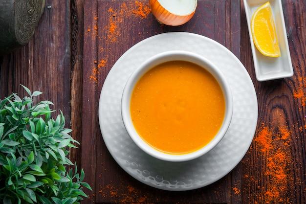 Vista superior sopa de lentejas con cebolla y limón horizontal