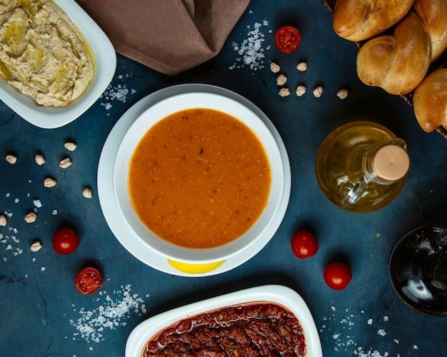 Vista superior de sopa de lentejas y guarniciones y pan