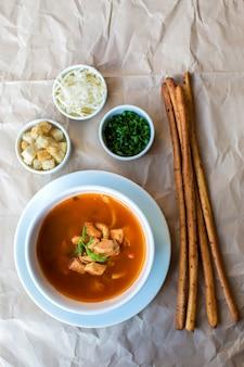 Vista superior de sopa de mariscos servida con palitos de pan y cubos, queso rallado, hierbas