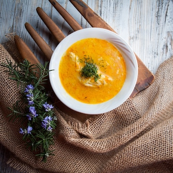 Vista superior sopa de pollo con hojas de romero y verduras en el tablero de alimentos