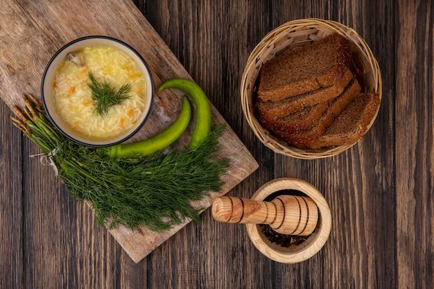 Vista superior de la sopa de pollo orzo en un tazón y pimientos con eneldo en la tabla de cortar y una canasta de rebanadas de pan de centeno con pimienta negra sobre fondo de madera