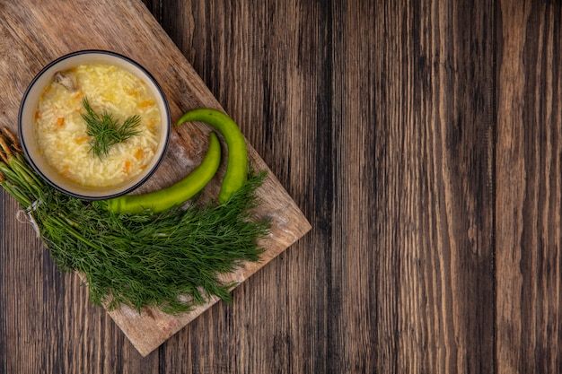 Vista superior de la sopa de pollo orzo en un tazón y pimientos con eneldo en la tabla de cortar sobre fondo de madera con espacio de copia