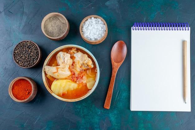 Vista superior de sopa de pollo con patatas junto con condimentos de sal pimienta y bloc de notas en el fondo azul oscuro sopa carne comida cena