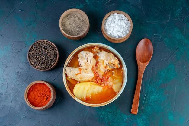 Vista superior de sopa de pollo con patatas junto con condimentos de sal pimienta en el fondo azul oscuro sopa carne comida cena