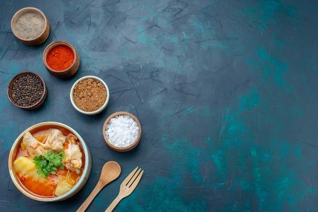 Vista superior de sopa de pollo con pollo y verduras en el interior junto con condimentos en el escritorio azul oscuro sopa carne comida cena pollo