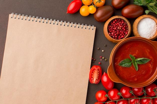 Vista superior de la sopa de tomate de invierno en un tazón con cuaderno