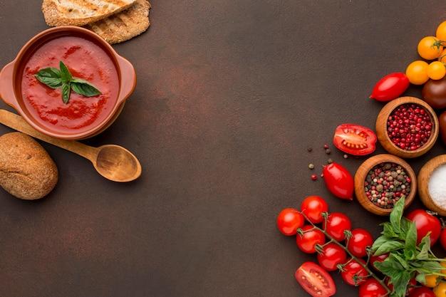 Vista superior de la sopa de tomate de invierno en un tazón con tostadas y copie el espacio