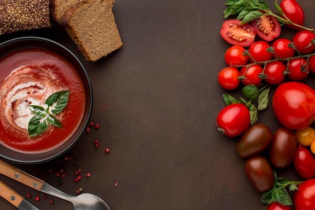 Vista superior de la sopa de tomate de invierno en un tazón con tostadas y cucharas