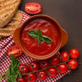 Vista superior de la sopa de tomate de invierno en un tazón con tostadas y mantel