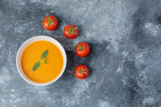Vista superior de la sopa de tomate en un tazón de cerámica blanca con tomates frescos en la mesa gris.