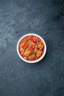 Vista superior de sopa de verduras con carne dentro de la placa en gris