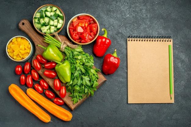 Vista superior del soporte para platos con verduras encima y cerca de él y el bloc de notas en el costado sobre fondo gris oscuro