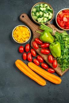 Vista superior del soporte para platos con verduras encima y cerca sobre fondo gris oscuro