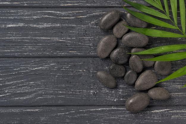 Vista superior spa bienestar piedras con hojas sobre la mesa
