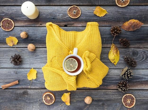 Vista superior suéter amarillo sobre fondo de madera