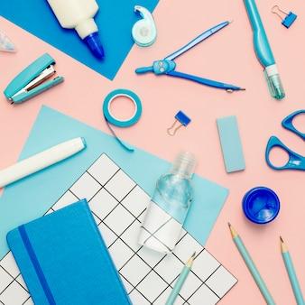 Vista superior de suministros azules sobre fondo rosa