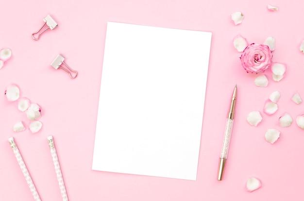 Vista superior de suministros de oficina rosa con pétalos de rosa
