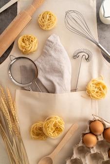 Vista superior de suministros con pasta e ingredientes en delantal