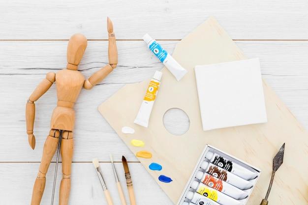 Vista superior de suministros de pintura con maniquí de madera