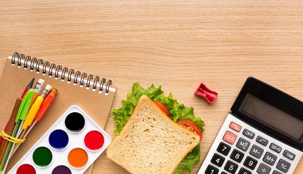 Vista superior de suministros de regreso a la escuela con calculadora y sandwich