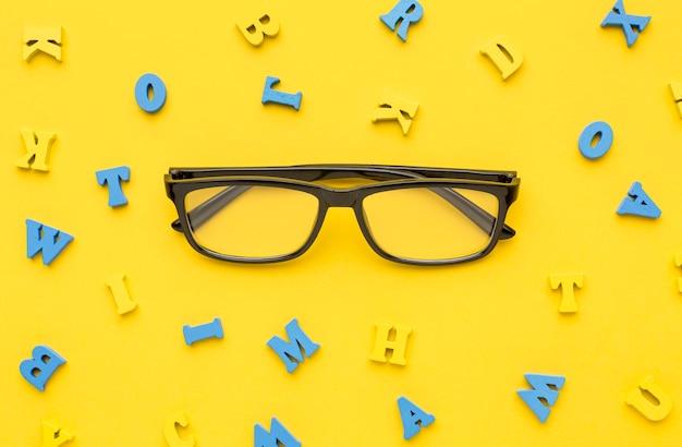 Vista superior de los suministros de regreso a la escuela con gafas y letras