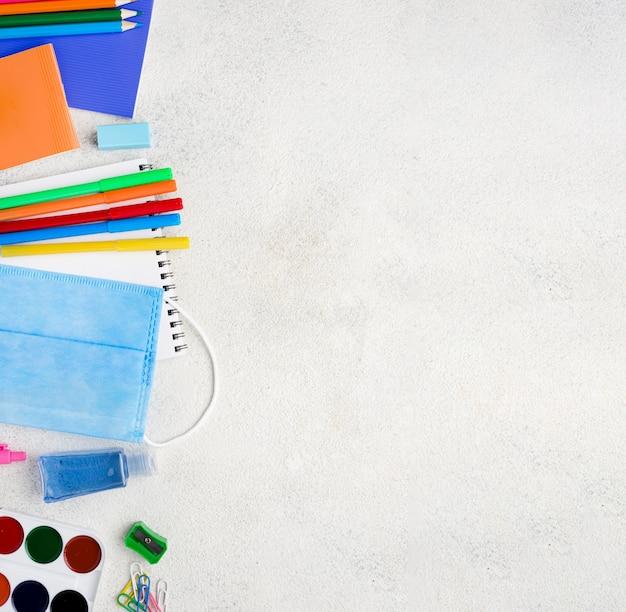 Vista superior de suministros para el regreso a la escuela con lápices y mascarilla médica