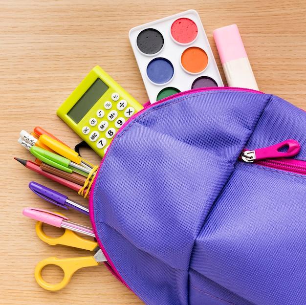 Vista superior de suministros de regreso a la escuela con mochila