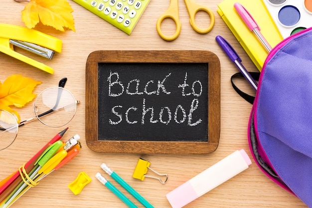 Vista superior de los suministros de regreso a la escuela con pizarra y backpacl