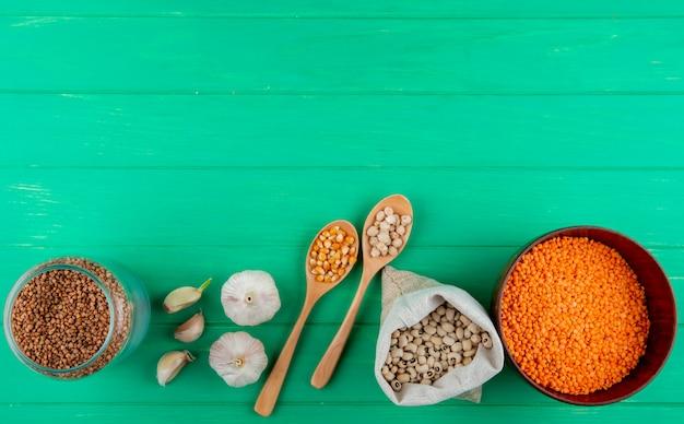 Vista superior del surtido de cereales y legumbres: alforfón, semillas de maíz, garbanzos, frijoles y lentejas rojas en una superficie de madera verde con espacio de copia