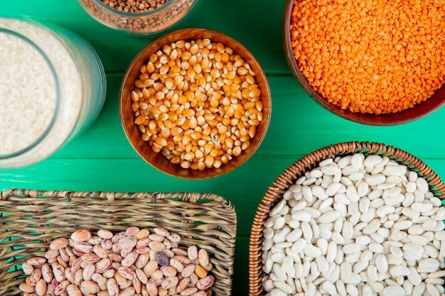 Vista superior del surtido de cereales y legumbres: granos de maíz, lentejas rojas, arroz y trigo sarraceno