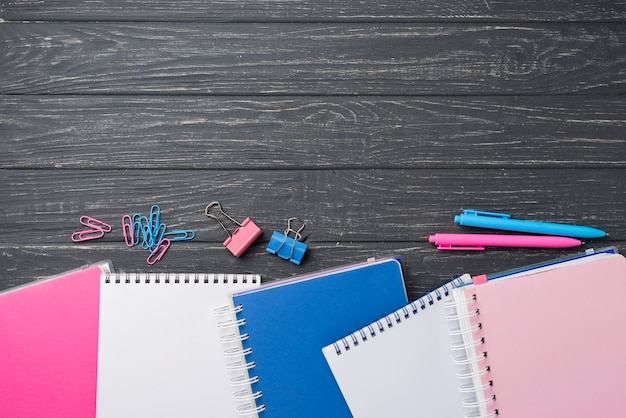 Vista superior de surtido en cuadernos de colores con bolígrafos y clips