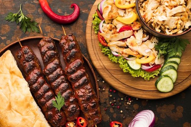 Vista superior del surtido de deliciosos kebabs con verduras y hierbas.