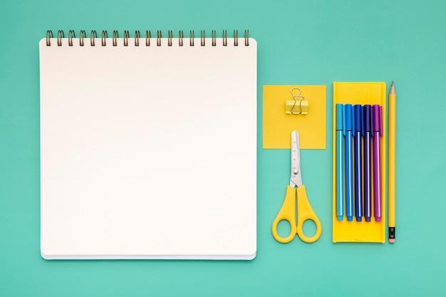 Vista superior surtido de elementos de escritorio con cuaderno vacío