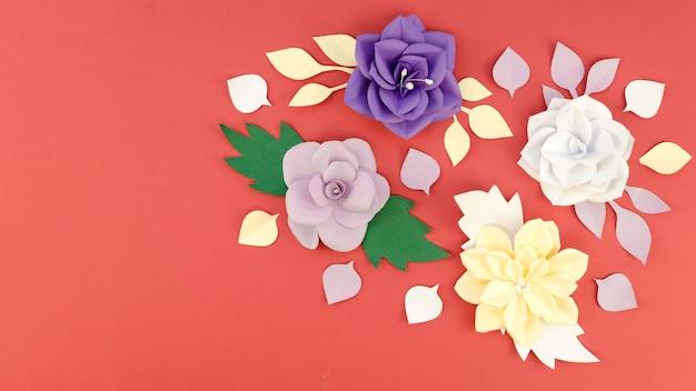Vista superior surtido con flores de papel y fondo rojo.
