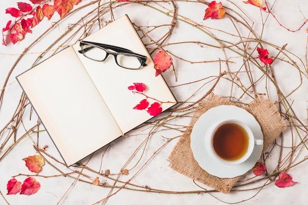 Vista superior de surtido otoñal con café y cuaderno abierto.