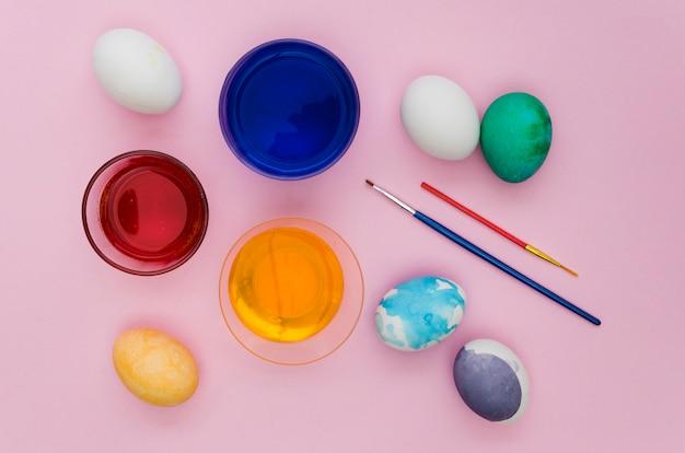Vista superior de surtido de pintura de huevo para pascua con pinceles
