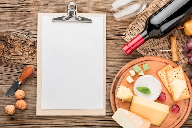 Vista superior surtido de quesos gourmet con copa de vino y bloc de notas en blanco