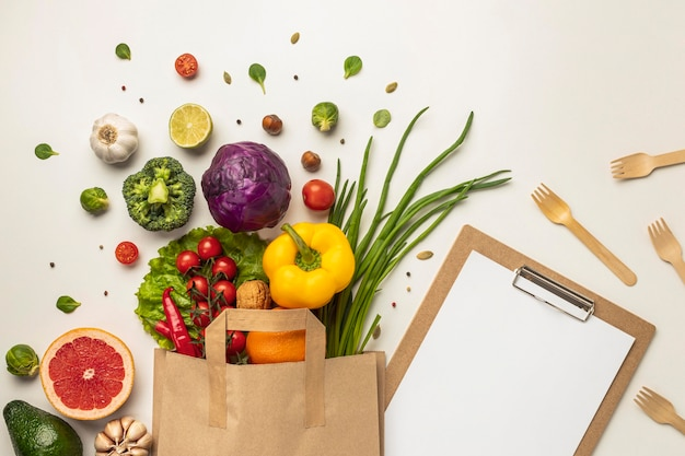 Vista superior del surtido de verduras en bolsa de papel con portapapeles